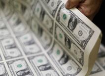 Billetes de 1 dólar en la Casa de la Moneda de Estados Unidos en Washington, nov 14 2014.  El dólar se aproximó a un máximo nivel en cuatro años y medio frente a una cesta de monedas el lunes debido a que los operadores especulaban que bancos centrales expandirían aún más la política monetaria para ayudar a sus economías, pese a que eso afectaría a sus monedas.  REUTERS/Gary Cameron