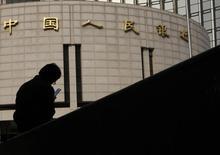 Un hombre frente de la sede del banco central de China en Beijing. Imagen de archivo, 17 octubre, 2013. El banco central de China recortó el martes el rendimiento de un índice clave de dinero a corto plazo por cuarta vez este año, en momentos en que los reguladores intensifican los esfuerzos para reducir las presiones sobre la financiación a las firmas locales.  REUTERS/Kim Kyung-Hoon