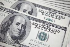 Долларовые купюры в банке в Сеуле 20 сентября 2011 года. Доллар снизился к евро и иене в среду после выхода данных, подразумевающих, что экономический рост в США, возможно, замедляется в четвертом квартале 2014 года. REUTERS/Lee Jae-Won