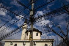 Электрические провода на фоне мечети в Симферополе 14 марта 2014 года. Украина, столкнувшаяся с топливным кризисом перед зимой, отключила три из четырех линий передачи электроэнергии в Крым, и попыталась разрешить украинским компаниям покупать электричество у России после прекращения поставок угля. REUTERS/Thomas Peter