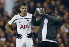 Torcedor entra em campo e tira 'selfie' com jogador do Tottenham Hotspur Erik Lamela em jogo da Liga Europa na quinta-feira.  REUTERS/Eddie Keogh