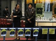 Sales persons wait for customers at a jewelry store at a road occupied by pro-democracy protesters at Mongkok shopping district in Hong Kong October 27, 2014. REUTERS/Bobby Yip
