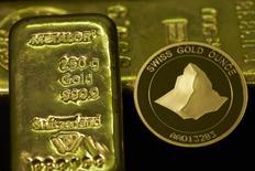 Золотая монета и слитки в нумизматическом магазине Jolliet в Женеве 19 ноября 2014 года. Цены на золото держатся около $1.200 за унцию при поддержке цен на нефть, но укрепление доллара и оптимистичные прогнозы для американской экономики мешают росту котировок. REUTERS/Denis Balibouse