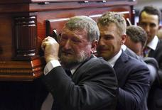 Gregory Hughes (front), the father of Australian cricketer Phillip Hughes, cries as he carries his son's casket past mourners after his funeral service in the town of Macksville, located north of Sydney, December 3, 2014.  REUTERS/Cameron Spencer/Pool