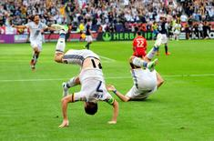 Dec 7, 2014; Los Angeles, CA, USA; Los Angeles Galaxy forward Robbie Keane (left) and forward Alan Gordon (right) do somersaults as Keane scores a goal against the New England Revolution  in the overtime during the 2014 MLS Cup final at Stubhub Center. Mandatory Credit: Gary A. Vasquez-USA TODAY Sports