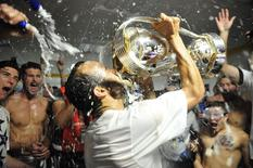 Los Angeles Galaxy forward Landon Donovan (10) celebrates by drinking out of the MLS Cup championship trophy in the locker room after defeating the New England Revolution in the 2014 MLS Cup final at Stubhub Center. Mandatory Credit: Gary A. Vasquez-USA TODAY Sports