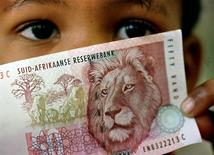 A South African child holds a 50 rand note  in a file photo.