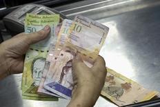 Un cajero cuenta bolívares en un supermercado en Caracas, sep 9 2014. Un reconocido economista opositor en Venezuela dijo que el Producto Interno Bruto (PIB) del país se habría contraído un 4,2 por ciento en los primeros nueve meses del año, lo que sería su mayor retroceso desde el 2009, en medio de la ausencia de cifras oficiales sobre la actividad económica.  REUTERS/Carlos Garcia Rawlins