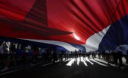 Estudantes cubanos carregam uma bandeira gigante de seu país durante passeata em Havana. 27/11/2014. REUTERS/Enrique De La Osa