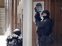Сотрудники полиции у кафе Lindt в Сиднее 15 декабря 2014 года. Вооруженный человек захватил в заложники неустановленное число людей в кафе Lindt в центре Сиднея, парализовав крупнейший город Австралии. REUTERS/Jason Reed