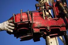 El crudo Brent tocó nuevos mínimos de cinco años de casi 60 dólares por barril el lunes después de que la OPEP reafirmó su determinación de no reducir la producción pese a un exceso global de suministros, aunque el referencial del Mar del Norte escaló más tarde para cotizar cerca de 63 dólares. En la imagen, un hombre trabaja en un campo petrolero en  McKenzie , Dakota del Norte, el 12 de marzo de 2013. REUTERS/Shannon Stapleton