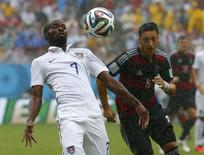 DaMarcus Beasley of the U.S. (L) fights for the ball with Germany's Mesut Ozil during their 2014 World Cup Group G soccer match at the Pernambuco arena in Recife June 26, 2014.  REUTERS/Tony Gentile