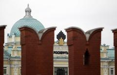 The logo of Russia's top crude producer Rosneft is seen at the company's headquarters, behind the Kremlin wall, in central Moscow May 27, 2013. Rosneft, Russia's No. 1 oil producer, said on Friday its second-quarter net income rose by almost five times, year-on-year, to 172 billion roubles ($4.9 billion), beating analyst forecasts, thanks to a stronger rouble. Picture taken May 27, 2013. REUTERS/Sergei Karpukhin/Files (RUSSIA - Tags: ENERGY BUSINESS COMMODITIES)