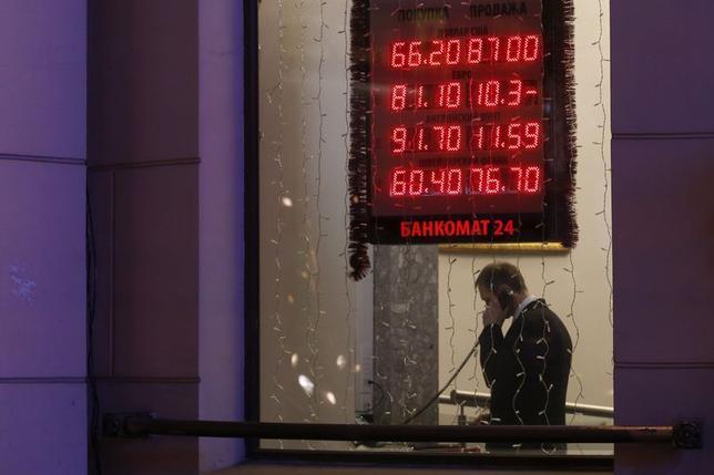 12月16日、外国為替市場はルーブルが一段安となった。写真はモスクワの為替表示と男性。同日撮影(2014年 ロイター/Maxim Zmeyev)