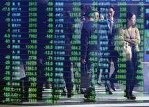 Transeúntes se ven reflejados en una pantalla que muestra índices económicos en Tokio. Imagen de archivo, 17 noviembre, 2014. El índice Nikkei de la bolsa de Tokio subió el miércoles, alejándose de un mínimo en seis semanas y media luego de que la esperanza de una continuación de la postura moderada de la Reserva Federal de Estados Unidos ayudó a impulsar la confianza. REUTERS/Issei Kato