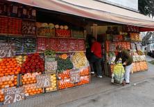 Una persona realiza unas compras en una frutería en Buenos Aires, jul 31 2014. El superávit comercial de Argentina habría caído un 13,5 por ciento interanual en noviembre, debido a menores exportaciones y a las vigentes restricciones a las importaciones que impone el Gobierno para evitar una fuga de capitales. REUTERS/Enrique Marcarian
