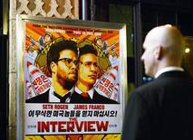 """A security guard stands at the entrance of United Artists theater during the premiere of the film """"The Interview"""" in Los Angeles, California in this December 11, 2014 file photo. REUTERS/Kevork Djansezian/Files"""