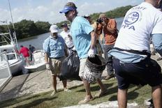 """U.S. artist and conservationist Guy Harvey (C) leads a group of volunteers along the San Juan estuary system for the second """"mega cleanup"""" of garbage from the waterway, in San Juan, in this October 26, 2013 file picture.      REUTERS/Alvin Baez/Files"""