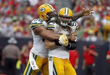 Dec 21, 2014; Tampa, FL, USA; Green Bay Packers outside linebacker Clay Matthews (52) is congratulated by defensive end Mike Neal (96) after he sacked Tampa Bay Buccaneers quarterback Josh McCown (not pictured) during the second half at Raymond James Stadium. Kim Klement-USA TODAY Sports