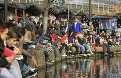 Unas personas sentadas junto a un canal en la zona londinense de Camden, Inglaterra, mar 11 2012. El dueño del Mercado de Camden, una popular atracción turística de Londres que convoca a cerca de 100.000 personas cada fin de semana, hizo su debut en la bolsa el lunes, en la mayor apertura del año en el Alternative Investment Market (AIM). REUTERS/Olivia Harris