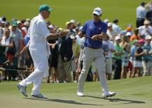 Australia's Adam Scott takes his putter from caddie Steve Williams on the second hole during the third round of the Masters golf tournament at the Augusta National Golf Club in Augusta, Georgia April 12, 2014. REUTERS/Brian Snyder