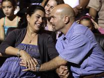 "Gerardo Hernandez , one of the so-called ""Cuban Five"", reacts with his wife Adriana Perez (L) during Cuban musician Silvio Rodriguez's concert in Havana December 20, 2014.  REUTERS/Enrique De La Osa"