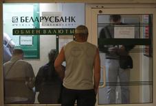 Люди в очереди в пункт обмена валюты в Минске 24 мая 2011 года. Национальный банк Белоруссии рекомендовал коммерческим банкам повысить курс покупки наличной валюты на 20-25 процентов, не меняя официального курса продажи, чтобы подавить черный рынок валюты, сказали Рейтер источники в двух банках. REUTERS/Vasily Fedosenko