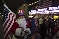 """Matt Ornstein, dressed in a Santa Claus costume, holds an American flag as fans line up at the Silent Movie Theatre for a midnight screening of """"The Interview"""" in Los Angeles, California December 24, 2014.  REUTERS/Jonathan Alcorn"""