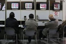 Розничные инвесторы в брокерской конторе в Шанхае 24 декабря 2014 года. Азиатские фондовые рынки выросли в пятницу за счет улучшения экономической статистики и подъема на фондовом рынке США. REUTERS/Aly Song