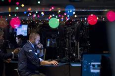 El operador Kevin Lodewick trabajando en la bolsa de Wall Street en Nueva York, dic 22 2014. Las acciones subían el viernes en la bolsa de Nueva York, con máximos históricos en los principales índices referenciales y en camino para registrar una segunda ganancia semanal, aunque el volumen negociado era escaso porque muchos operadores siguen fuera de sus puestos por los feriados de Navidad.            REUTERS/Carlo Allegri