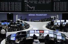 Traders are pictured at their desks in front of the German share price index DAX board at the Frankfurt stock exchange on December 29, 2014. REUTERS/Remote/Stringer