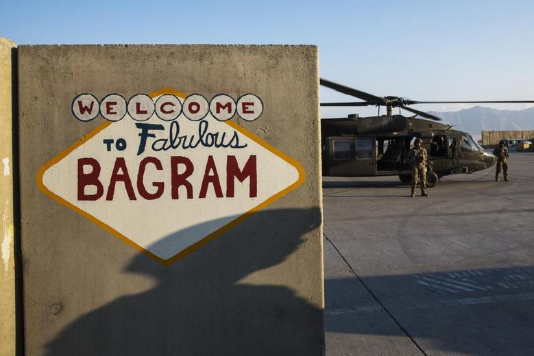 A U.S. soldier from the 3rd Cavalry Regiment casts a shadow on a sign painted on a blast barrier at Bagram Air Field in the Parwan province of Afghanistan December 23, 2014. REUTERS/Lucas Jackson