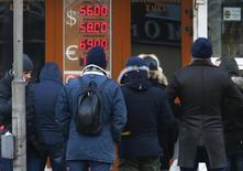 Очередь в обменный пункт в Москве 29 декабря 2014 года. Рубль растет на неактивных торгах вторника к доллару и евро на рынке с небольшим количеством участников и без вмешательства Центробанка РФ, игнорируя снижение нефтяных котировок к отметке $57. REUTERS/Sergei Karpukhin