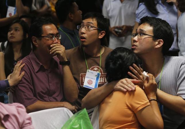 12月30日、消息不明となっているエアアジア機の捜索活動を行っているインドネシア当局者はボルネオ島沖で遺体や荷物を確認した。写真はスラバヤに集まった搭乗者の家族ら(2014年 ロイター/Beawiharta)