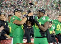 Jan 1, 2015; Pasadena, CA, USA; Oregon Ducks quarterback Marcus Mariota (8) and linebacker Tony Washington (91) celebrate with the Leishman Trophy after defeating the Florida State Seminoles in the 2015 Rose Bowl college football game at Rose Bowl. Kelvin Kuo-USA TODAY Sports