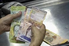 Una cajera cuenta bolívares en un supermercado en Caracas, sep 9 2014. La deuda venezolana caía el martes presionada por la baja de los precios del crudo y la creciente preocupación en el mercado por la capacidad del país petrolero para pagar sus deudas, ante la timidez del Gobierno para imponer medidas de ajuste económico. REUTERS/Carlos Garcia Rawlins