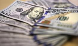 Долларовые купюры в Йоханнесбурге 13 августа 2014 года. Курс доллара снижается, так как инвесторы разочарованы неожиданным сообщением о падении уровня заработной платы в США. REUTERS/Siphiwe Sibeko