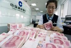 Сотрудник отделения китайского банка China Construction Bank считает юани в городе Хуаян в провинции Цзянсу. 10 июня 2014 года. Осторожные китайские банки выдали в декабре намного меньше кредитов, чем ожидалось, несмотря на неожиданное сокращение процентной ставки Центробанка. REUTERS/China Daily