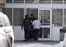 Police enter the entrance of a crime scene in St. Albert, Alberta, where two RCMP officers sustained significant injuries after being shot at the Apex Casino, January 17, 2015.  REUTERS/Dan Riedlhuber
