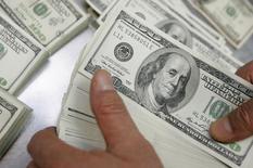 Работник банка Korea Exchange Bank считает стодолларовые купюры. Сеул, 6 января 2010 года. Чистый отток частного капитала из РФ в 2014 году составил рекордные $151,5 миллиарда, перегнав кризисный 2008 год, когда из страны утекло $133,6 миллиарда, свидетельствует оценочные данные платежного баланса РФ, опубликованные ЦБР. REUTERS/Choi Bu-Seok