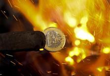 Монету евро плавят в кузнице в Скопье. 6 декабря 2011 года. Золотовалютные резервы РФ потеряли за неделю $6,8 миллиарда и достигли минимальных значений с середины марта 2009 года, в основном за счет отрицательной переоценки валют, а также из-за операций ЦБ по предоставлению валютной ликвидности на внутреннем рынке. REUTERS/Ognen Teofilovski