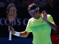 Roger Federer of Switzerland gestures to Andreas Seppi of Italy after hitting the net-cord during their men's singles third round match at the Australian Open 2015 tennis tournament in Melbourne January 23, 2015. REUTERS/Issei Kato