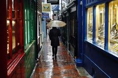 A woman carrying an umbrella walks through The Lanes shopping area in Brighton, southern England, in this January 8, 2015 file photo. REUTERS/Luke Macgregor/Files