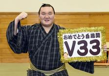 """Mongolian-born grand sumo champion Yokozuna Hakuho poses for photos with a board reading """"Congrats Hakuho V33"""" after winning the New Year Grand Sumo Tournament in Tokyo January 23, 2015, in this photo taken by Kyodo.  Mandatory Credit REUTERS/Kyodo"""