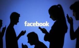 Pessoas posam para foto em frente a projeção da logomarca do Facebook. 29/10/2014 REUTERS/Dado Ruvic