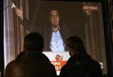 Personas observan una pantalla donde el líder del partido Syriza realiza un discurso luego de ganar las elecciones en Atenas, 25 enero, 2015. Europa mostró el lunes la voluntad de dar a Atenas más tiempo para pagar sus deudas, si bien dio pocas señales de que las vaya a perdonar, como exige el nuevo Gobierno griego. REUTERS/Yannis Behrakis