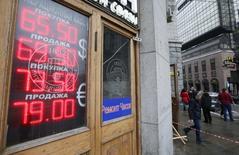 """Вывеска пункта обмена валюты в Москве 27 января 2015 года. Рубль дорожает во вторник, восстанавливаясь после значительного падения накануне вечером в ответ на понижение кредитного рейтинга России до """"мусорного"""" статуса. REUTERS/Maxim Zmeyev"""