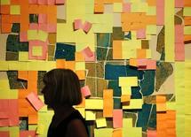 Женщина проходит мимо работы, сделанной из Post-it, на Трафальгарской площади в Лондоне 11 августа 2013 года. Квартальная прибыль американской 3M Co выросла на 2 процента, оказавшись хуже прогнозов из-за укрепления доллара. REUTERS/Luke MacGregor