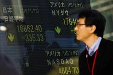 Un hombre observa una pantalla electrónica que muestra índices económicos en Tokio. Imagen de archivo, 13 enero, 2015. Las bolsas de Asia extendían sus pérdidas el jueves después de que la Reserva Federal adoptó una visión optimista sobre la economía de Estados Unidos y sugirió que se encamina a elevar las tasas de interés este año, pese a un panorama global incierto. REUTERS/Thomas Peter