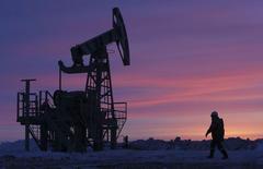 Un trabajador pasa frente una extractora de petróleo cerca de Nikolo-Berezovka. Imagen de archivo, 28 enero, 2015.  Los precios del crudo continuarán bajando antes de recuperarse ligeramente en el segundo semestre y podrían promediar este año incluso menos que durante la crisis financiera mundial, mostró el viernes un sondeo de Reuters entre analistas. REUTERS/Sergei Karpukhin